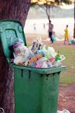 A lot of garbages contained in green wastebin that`s placed under a tree. Public trash background, Garbage waste in park full of a. Ll sort of trash Stock Image