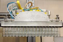 A lot of glass bottles hanging in a pneumatic gripper. Loading glass bottles from pallets. Stock Photos