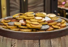 A lot of gold coins on a wooden barrel, the concept of wealth stock photo