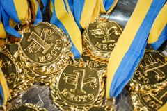 A lot of gold medals with yellow ribbons on a silver tray, awards of champions, sport achievements, first place. Prize for the winner, it is written on a medal Stock Photography
