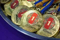 A lot of gold medals with yellow ribbons on a silver tray, awards of champions, sport achievements, first place, prize for the wi. Nner Royalty Free Stock Images
