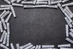 A lot of gray, plastic wall plugs, lying on a black background, flat view from above. royalty free stock images