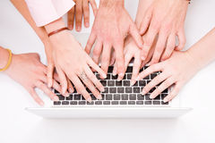Lot of hands with grey laptop. Computer on desk Stock Photo