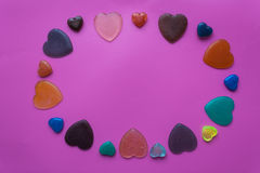 A lot of hearts on pink-purple background. Valentine`s Day postc. Colorful hearts made from epoxy resin. Pink-mauve background. Valentine`s Day postcard Royalty Free Stock Image
