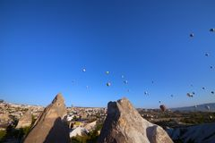 Lot of hot air balloons on blue clear sky and fairy chimneys rock formations. GOREM, CAPPADOCIA,TURKEY - MAY 07, 2013: Lot of multicolor hot air balloons on blue stock photography