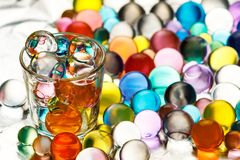 A lot of hydrogel balls on aluminum foil and a vodka pile filled with hydrogel balls Royalty Free Stock Photo