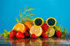 A lot of juicy citrus fruits, strawberries and mint and tarragon, on wet wooden boards, on top are yellow sunglasses, on a blue. Background, the concept of royalty free stock photo