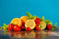 A lot of juicy citrus fruits, strawberries and mint on wet wooden boards, on a blue background, with water drops, the concept of. Summer and healthy nutrition stock image