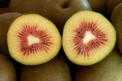 A section of a red kiwi cut in half. A lot of kiwi are piled up and a red kiwi cut in half is placed on it stock photo