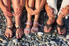 Lot of legs and hands on stones. Family with girl Royalty Free Stock Photography