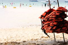 A lot of life jackets hanging on the beach. The concept of water safety. A lot of life jackets hanging on the beach. Rest on the sea and safety royalty free stock images