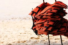 A lot of life jackets hanging on the beach. The concept of water safety. A lot of life jackets hanging on the beach. Rest on the sea and safety stock photo