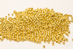 Gold beads on white Stock Photo