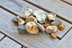 Lot of little rocks on wooden table Stock Photos