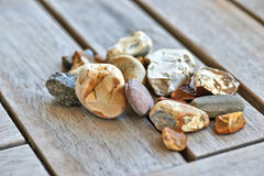 Lot of little rocks on wooden table Stock Photography