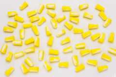 A lot of lying earplugs, for protection against noise in yellow and white, isolated on a white background with a clipping path. A lot of lying earplugs, for stock photos