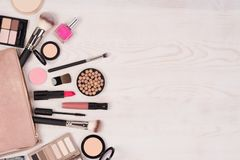 Makeup cosmetics and an open bag on white wooden background, top view with copy space. A lot of makeup cosmetics and an open pink bag on white wooden background stock images