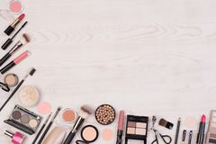 Makeup cosmetics such as eyeshadows, lipstick, mascara and makeup accessories on white, wooden background, top view with copy spac stock photos