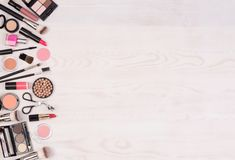 Makeup cosmetics such as eyeshadows, lipstick, mascara and makeup accessories on white, wooden background, top view with copy spac royalty free stock photography