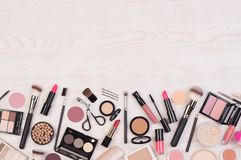 Makeup cosmetics such as eyeshadows, lipstick, mascara and makeup accessories on white, wooden background, top view with copy spac stock photography