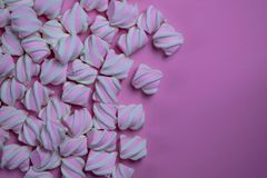 A lot of marshmallows are laid out on the side on a pink background. Free space for text, idea for design stock images