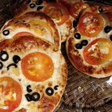 Mini pizzas. A lot of mini pizzas homemade thin crust dough and tons of topping ideas like tomatoes Royalty Free Stock Photos