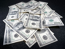 A lot of money. Heap of dollars greenback in dark background Stock Image
