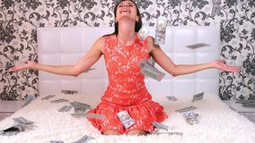 Lot of money flies in the air over a white bed with a beautiful girl. The concept of tremendous wealth. A lot of money flies in the air over a white bed with a stock video footage