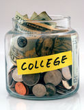 "A lot of money in a glass jar labeled College. A lot of money in a glass bottle labeled ""College Stock Photo"