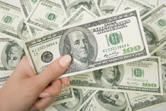 A lot of money (U.S. dollars), hand holding a hundred dollar Royalty Free Stock Image