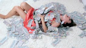 Lot of money on a white bed with a beautiful girl. The concept of tremendous wealth. Lot of money on a white bed with a beautiful girl. The concept of stock video