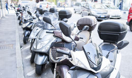 Lot of motor scooters parked in a row. Trieste ,Italy - April 22 2016 : Motorbike, motorcycle scooters parked in row in city street Stock Photos