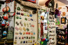 A lot of multi-colored earrings hanging against linen canvas, a mirror and other trinkets in the store with handmade goods in Lviv. LVIV, UKRAINE - SEPTEMBER 15 stock photo