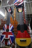 Multi-colored ukulele and guitars in a musical instrument store royalty free stock images