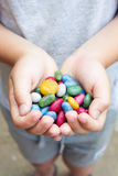 Lot of multicolored candies in the hands of a child Royalty Free Stock Image