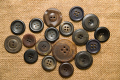 A lot of old buttons  on the old cloth Stock Image