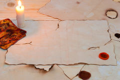 A lot of old papers on the table. Burning candle on a light table are paper Stock Images