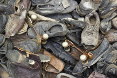 A lot of old trash shoes with pair of rusty roller skates.  Stock Photos