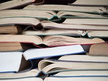 A lot of opened old and used hardback books or text books. Books and reading are essential for self improvement, gaining stock images