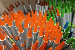 A lot of orange and green multicolored pencils close up stock photography