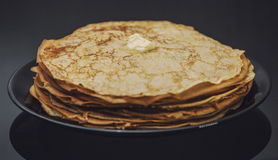 The lot of pancakes on black plate Royalty Free Stock Image