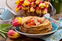 A lot of pancakes with red caviar, on a wooden table. A bouquet of tulips. Food for the traditional spring festival in Russia. Thin Russian pancakes with stock photo