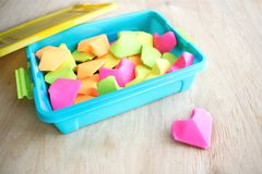 A lot of paper colorful origami heart in blue launch box and one. Pink heart. Origami paper hearts geometric volume. Colored paper hearts. Selective focus Royalty Free Stock Photo