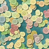 A lot of pastel multi colored vintage clothing buttons randomly scattered on the blue background - top view Stock Photo