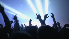 Lot of people clapping at rave party. Here is footage of people crowd partying at a concert or a night club. You can see dark silhouettes dancing, jumping and stock video footage