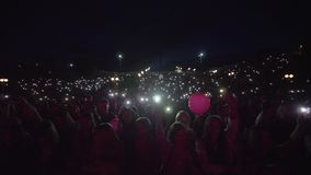 Lot people fans with flashlights on mobile phone waving hands and enjoy musical art during night outdoor concert on open