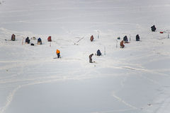 Lot of people fishing on the ice in winter. In the daytime Stock Image