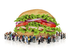 A lot of people are looking at a huge burger. Stock Photos