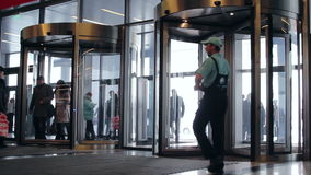 A lot of people pass through the glass revolving door every day stock video footage