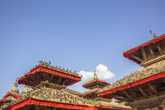 A lot of pigeons sit on the red roofs of Asian temples on the background of clean blue sky royalty free stock images